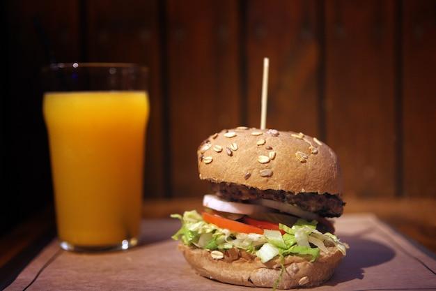 Grote huisgemaakte burger met gegrild vlees en jus d'orange. smakelijke hamburgerlunch met rundvlees. lunch eten.