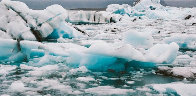 Grote ijsbergen die van de tong van een gletsjer worden losgemaakt die de kust in ijsland bereiken