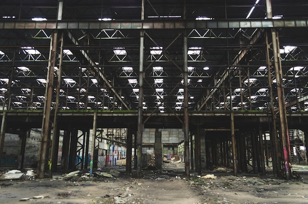 Grote industriële hal verlaten magazijn, fabriek met een hoop afval.