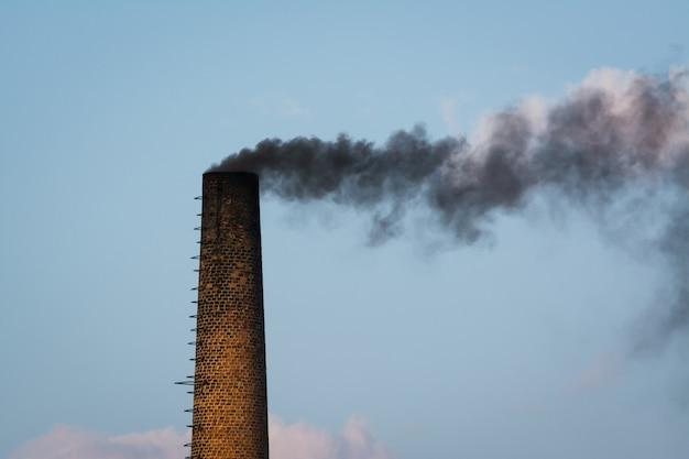Grote industriële pijp gemaakt van baksteen met zwarte rook naar buiten