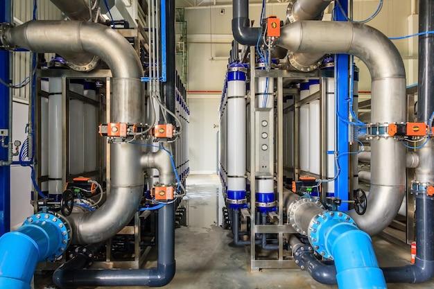 Grote industriële waterbehandeling en stookruimte. glanzende stalen metalen buizen en blauwe pompen