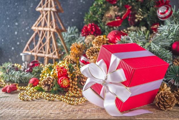 Grote kerst geschenkdoos met lint, ion feestelijke kersttafel, met decoratie en speelgoed, sneeuweffect Premium Foto