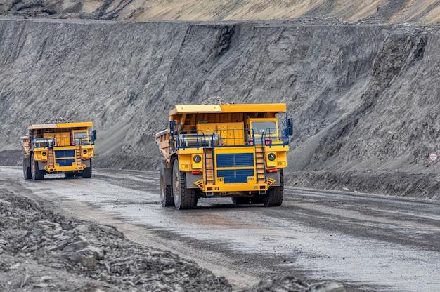 Grote kiepwagen. transportsector. een mijnbouwvrachtwagen rijdt langs een bergweg. de vrachtwagen van de steengroeve vervoert gedolven kolen.