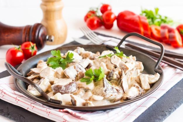 Grote koekenpan met witte champignons en roomsaus close-up.