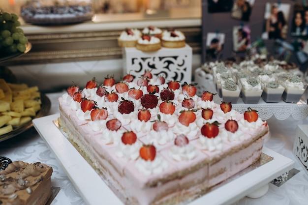 Grote koekjescake met room en aardbeien op porties gesneden
