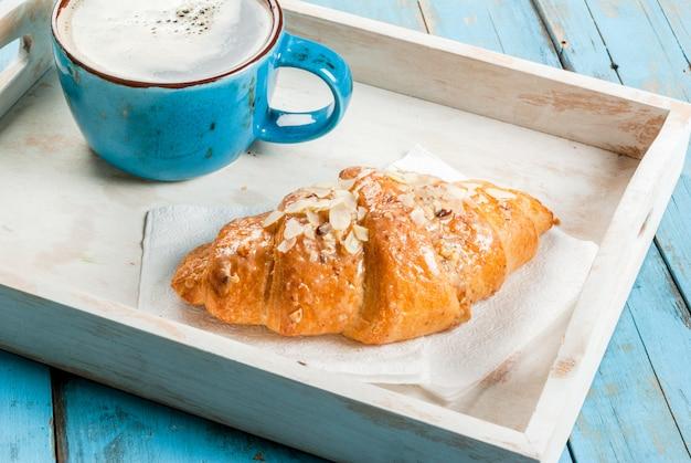 Grote koffiemok, croissant en krant