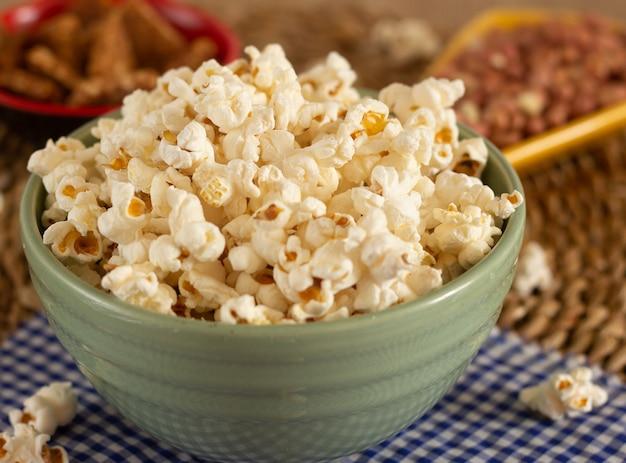 Grote kom vol popcorn omringd door pinda's snoepjes op de onscherpe achtergrond