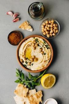 Grote kom zelfgemaakte hummus gegarneerd met kikkererwten, rode paprika, peterselie en olijfolie
