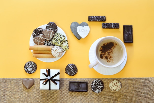 Grote kop met koffie met melk en schuim, chocoladeschilferkoekjes, wafels op een bord