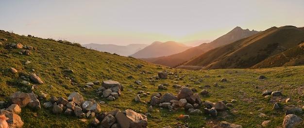 Grote kwartsh rotsen op een bergweide. zonsondergang in de bergen.