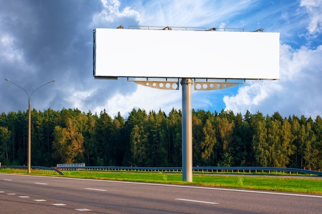 Grote lege mockup billboard langs een snelweg met bos op achtergrond van blauwe hemel met mooie wolken.
