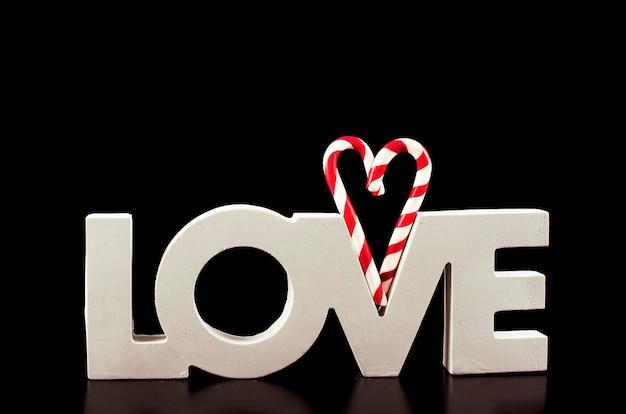 Grote letters liefde en hart lollipop geïsoleerd op zwart