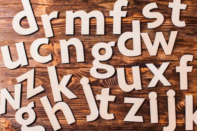 Grote letters van het alfabet zijn chaotisch verspreid over houten achtergrond. concept van onderwijs