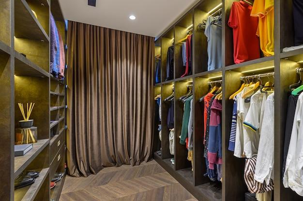 Grote luxe herengarderobe met verschillende kledingschoenen en accessoires, vooraanzicht