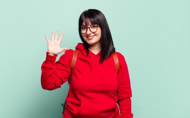 Grote maat mooie vrouw die vriendelijk glimlacht en er vriendelijk uitziet, nummer vijf of vijfde toont met de hand naar voren, aftellend