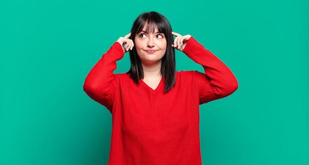 Grote maat, mooie vrouw die zich verward of twijfelt, zich concentreert op een idee, hard nadenkt, op zoek is naar ruimte aan de zijkant
