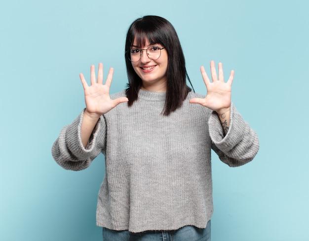 Grote maat mooie vrouw glimlachte en ziet er vriendelijk uit, nummer tien of tiende met de hand naar voren, aftellend