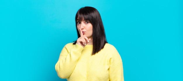 Grote maat mooie vrouw vraagt om stilte en stilte, gebaart met de vinger voor de mond, zegt shh of houdt een geheim
