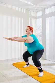 Grote maat vrouw doet squats