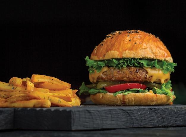 Grote mac-hamburger en aardappels stokken op een donkere houten bord.