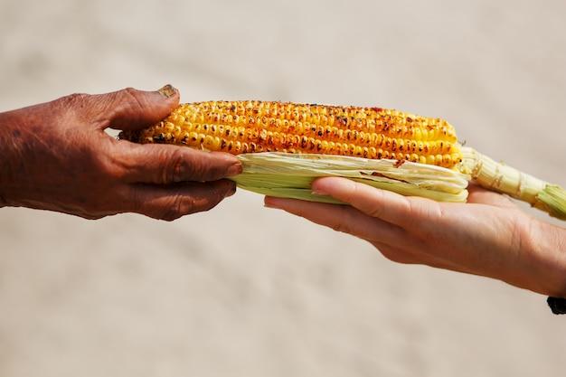 Grote maïskolf op de grill. close-up van de hand van een indiase vrouw geeft de maïs door aan een wit meisje. aziatisch straatvoedsel. trolley op het strand goa