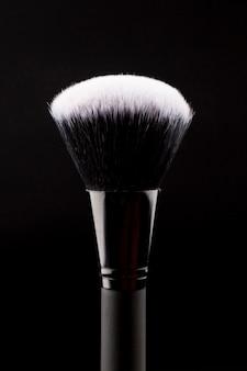 Grote make-upborstel op donkere achtergrond
