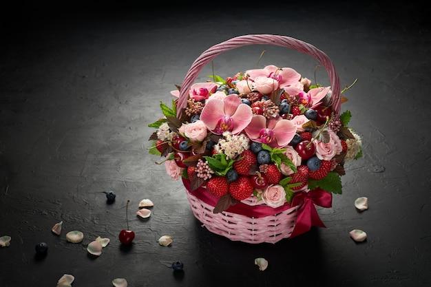 Grote mand gevuld met bloemen en fruit op zwart