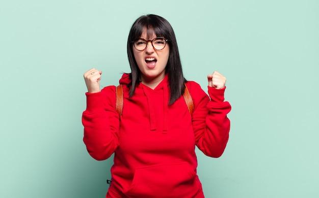 Grote maten mooie vrouw agressief schreeuwen met een boze uitdrukking of met gebalde vuisten om succes te vieren