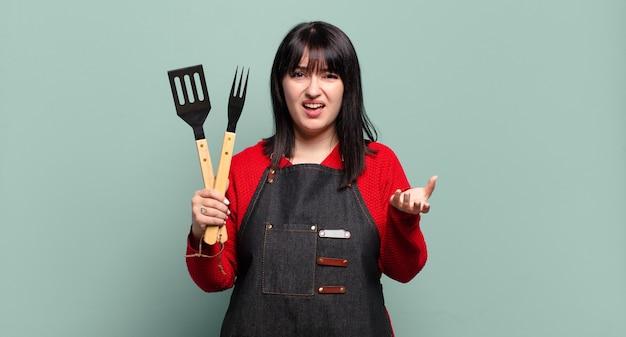 Grote maten mooie vrouw die boos, geïrriteerd en gefrustreerd kijkt, schreeuwend wtf of wat er mis is met jou
