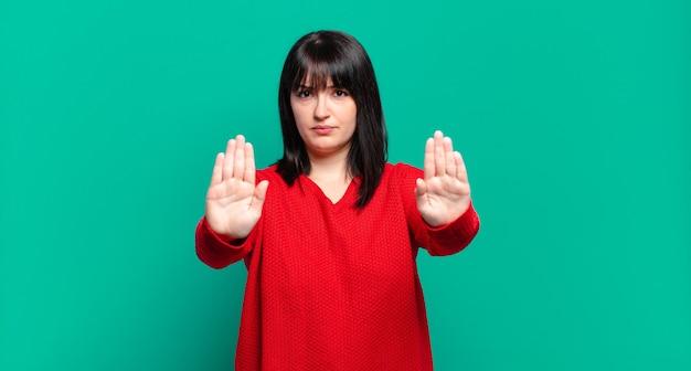 Grote maten mooie vrouw die er serieus, ongelukkig, boos en ontevreden uitziet en de toegang verbiedt of stop zegt met beide open handpalmen