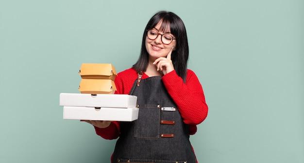 Grote maten mooie vrouw die gelukkig glimlacht en dagdroomt of twijfelt, opzij kijkt