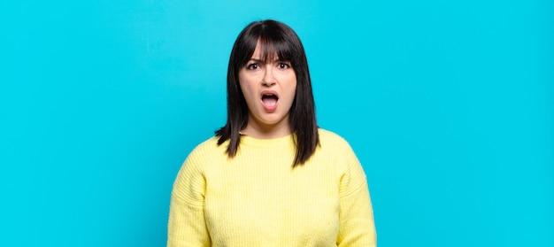 Grote maten mooie vrouw die geschokt, boos, geïrriteerd of teleurgesteld, met open mond en woedend kijkt