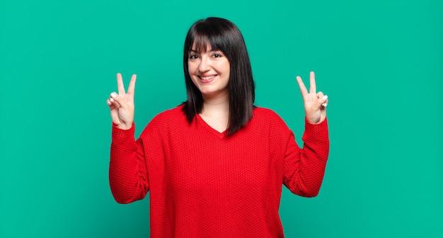 Grote maten mooie vrouw die lacht en er gelukkig, vriendelijk en tevreden uitziet, met beide handen een teken van overwinning of vrede