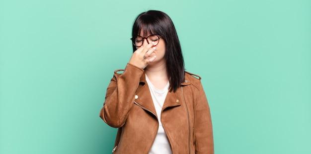 Grote maten mooie vrouw die walgt, neus vasthoudt om te voorkomen dat ze een vieze en onaangename stank ruikt