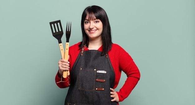 Grote maten mooie vrouw glimlachend gelukkig met een hand op de heup en zelfverzekerde, positieve, trotse en vriendelijke houding