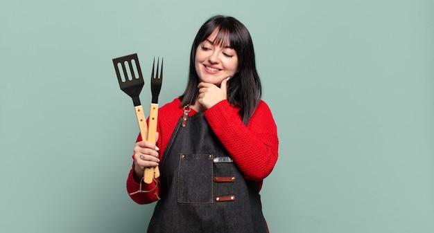 Grote maten mooie vrouw lachend met een gelukkige, zelfverzekerde uitdrukking met de hand op de kin, zich afvragend en opzij kijkend