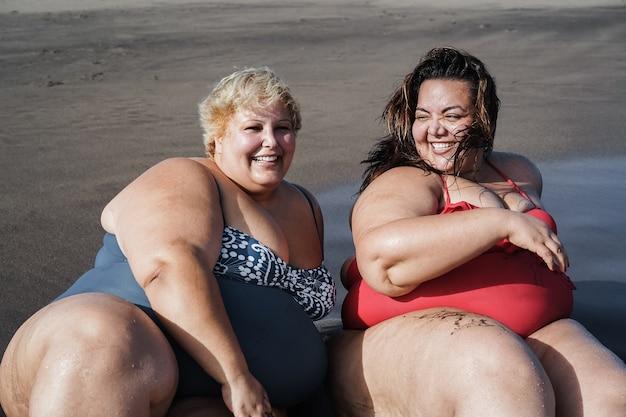 Grote maten vrouwen die op het strand zitten en zich vermaken tijdens de zomervakantie