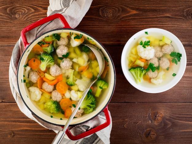 Grote metalen giet rode pan en bord met heerlijke warme soep van groenten en gehaktballen