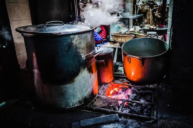 Grote metalen potten op brandende kolen in hanoi