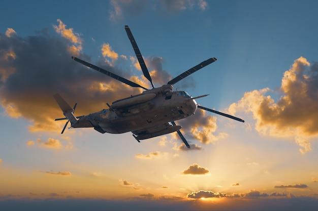 Grote militaire helikopter bij zonsondergangachtergrond