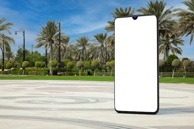 Grote moderne mobiele telefoon met leeg scherm als sjabloon voor uw ontwerp in lege stadsstraat met palmbomen extreme close-up. 3d-rendering