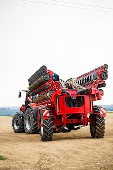 Grote moderne tractor om het veld na de winter klaar te maken voor het zaaien van graan