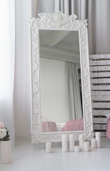 Grote mooie gesneden houten spiegel en kaarsen op de vloer in de slaapkamer