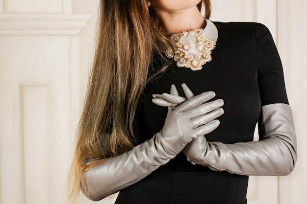 Grote mooie ketting gemaakt van gouden kralen en strass, grijze lange leren handschoenen