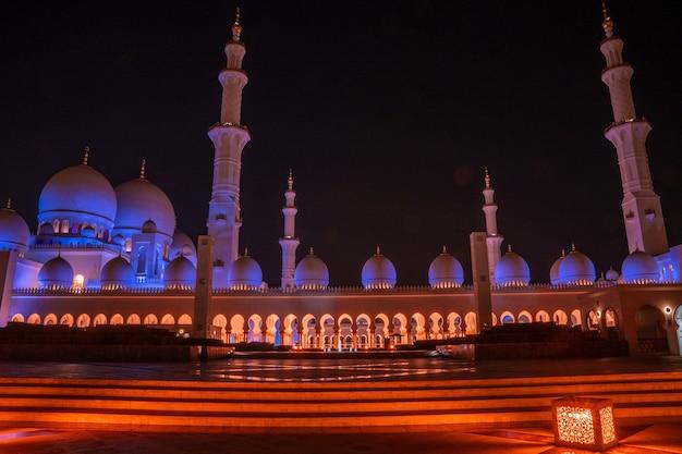 Grote moskee in abu dhabi bij nacht. panoramisch uitzicht op de buitenkant van sheikh zayed mosquein vae met epische bliksem.