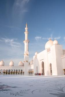 Grote moskee in abu dhabi in de avond tijdens zonsondergang. panorama van de buitenkant van sheikh zayed mosquein vae.