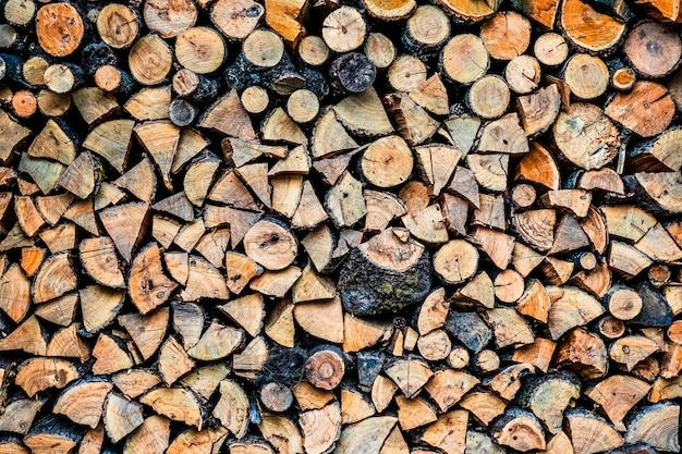 Grote muur van gestapelde houten logboeken die natuurlijke verkleuring tonen