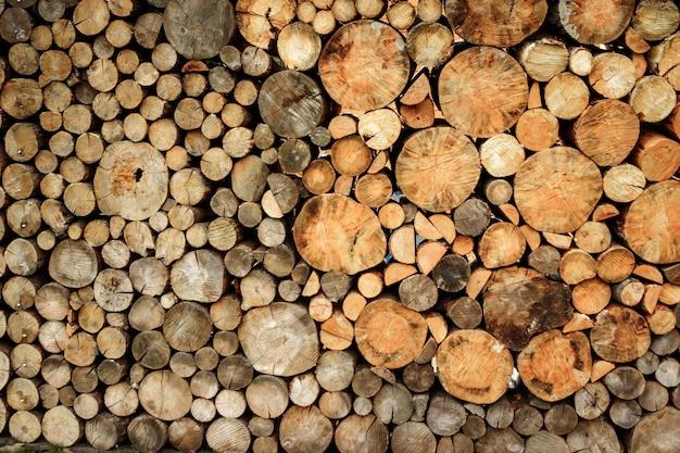 Grote muur van gestapelde houten logboeken die natuurlijke verkleuringachtergrond tonen