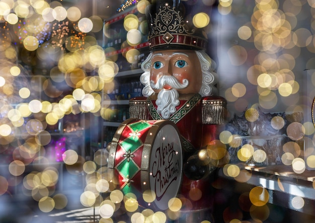 Grote notenkraker speelgoeddrummer onder wazige kerstverlichting