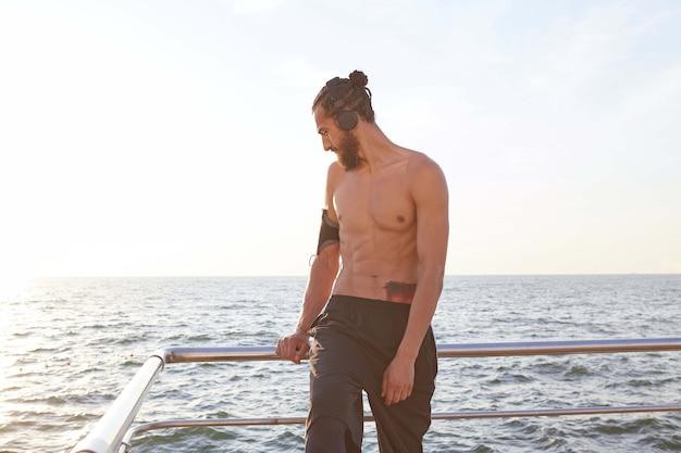 Grote ochtend! portret van jonge sportieve man met baard, rust na het joggen aan zee, luister favoriete mix op koptelefoon.